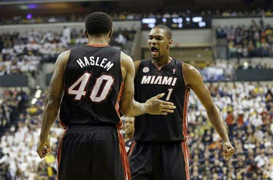 Miami Heat's Udonis Haslem (40) celebrates with Chris Bosh (1) after Haslem made a shot and was fouled during the first half of Game 3 of the NBA Eastern Conference basketball finals against the Indiana Pacers in Indianapolis, Sunday, May 26, 2013. (AP Photo/Nam H. Huh) Photo: AP / AP