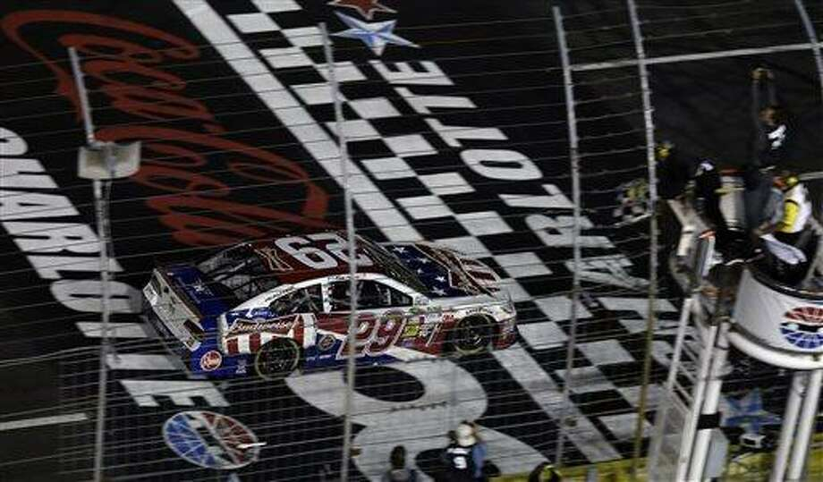 Kevin Harvick (29) takes the checkered flag to win the NASCAR Sprint Cup Series Coca-Cola 600 auto race at the Charlotte Motor Speedway in Concord, N.C., Sunday, May 26, 2013. (AP Photo/Gerry Broome) Photo: AP / AP