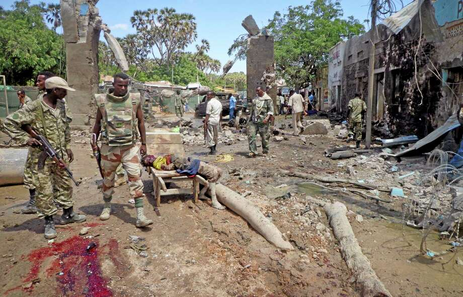 Security forces attend to the scene following a car bomb attack in Beledweyne, Somalia Tuesday, Nov. 19, 2013. Al-Qaida-linked militants detonated a car bomb at the entrance to a police station Tuesday in Beledweyne, near the Somalia-Ethiopia border, then opened fire with assault rifles and rocket-propelled grenades, officials said. (AP Photo) Photo: AP / AP