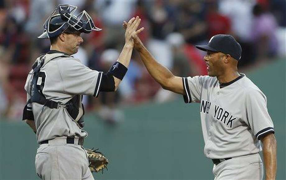 New York Yankees' Mariano Rivera, right, and Chris Stewart celebrate after defeating the Boston Red Sox 5-2 in a baseball game in Boston, Saturday, July 20, 2013. (AP Photo/Michael Dwyer) Photo: AP / AP