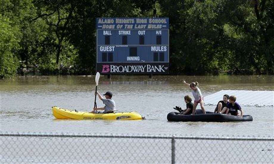 A kayaker pulls a raft with children around a flooded baseball park in San Antonio, Saturday, May 25, 2013, in San Antonio. San Antonio International Airport recorded more than nine inches of rain since midnight. (AP Photo/Eric Gay) Photo: AP / AP