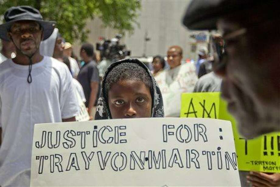 Jerald Eggleston, 10, holds a sign as he joined the more than 100 protestors organized outside the Bob Casey Federal Courthouse in Houston in reaction to the acquittal of neighborhood watch member George Zimmerman Tuesday, July 16, 2013. Protests have been held nationwide since jurors acquitted Zimmerman Saturday for the shooting death of unarmed teenager Trayvon Martin. Many of the posters carried by the protesters in Houston had a picture of Martin in his hooded sweatshirt. (AP Photo/Houston Chronicle, Johnny Hanson) Photo: ASSOCIATED PRESS / AP2013