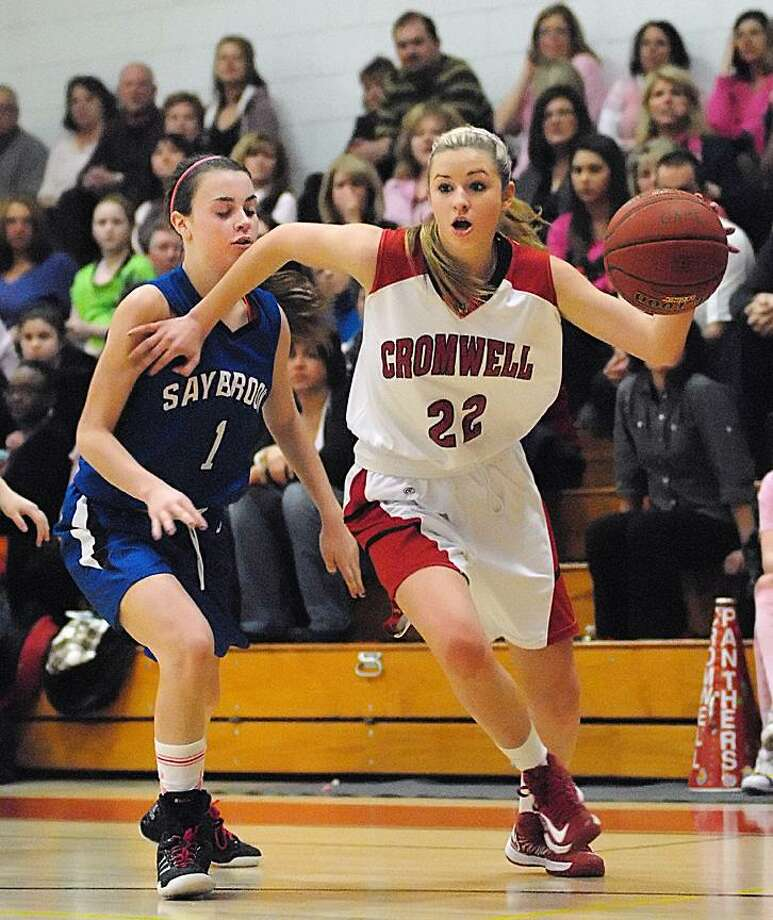 Catherine Avalone/The Middletown PressCromwell's Araya Lessard dribbles past Old Saybrook's Molly Beck during Friday nights game in Cromwell. Cromwell defeated Old Saybrook 51-40.