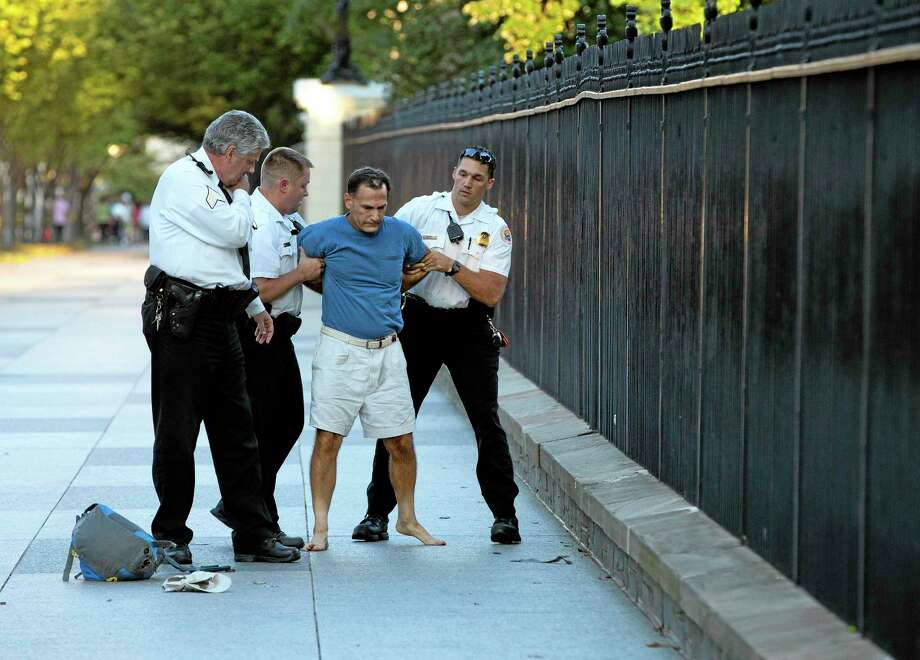 A man is taken into custody by uniformed Secret Service Police on Pennsylvania Avenue outside the White House on Monday, Sept. 16, 2013, in Washington. The Secret Service arrested the man for tossing lit firecrackers over the White House fence. (AP Photo/ Evan Vucci) Photo: AP / AP