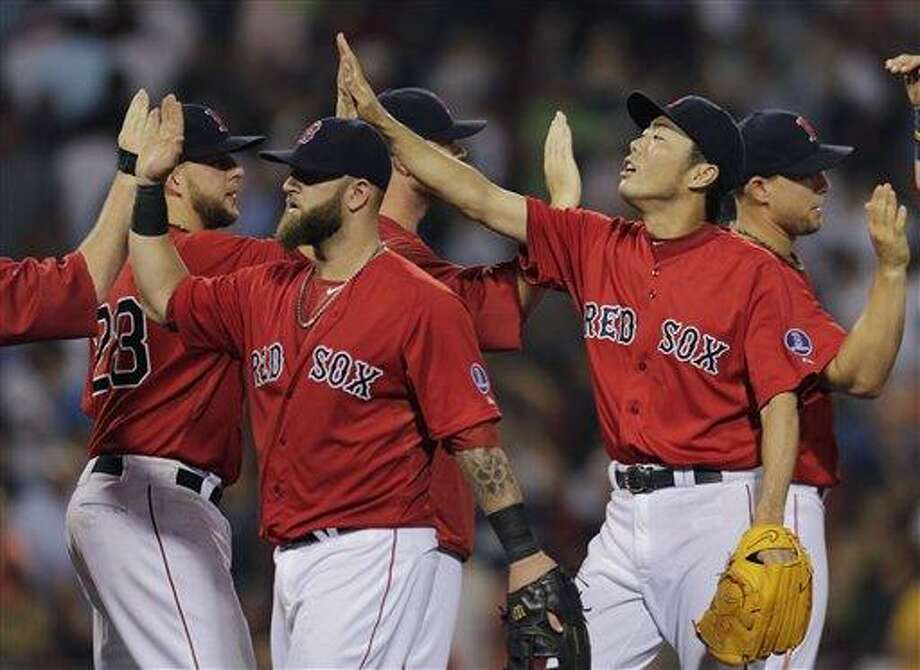 Boston Red Sox relief pitcher Koji Uehara is congratulated by teammates after beating the New York Yankees 4-2 during of a baseball game at Fenway Park, Friday, July 19, 2013, in Boston. (AP Photo/Charles Krupa) Photo: AP / AP