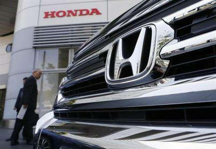 Visitors look at a Honda Motor Co.'s car displayed outside the company showroom in Tokyo April 26, 2013 REUTERS/Yuya Shino