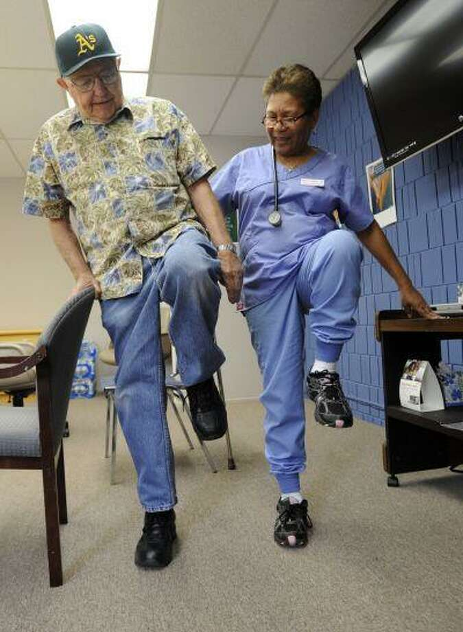 Rosita Gobbell, shows Blackie Blackwell, 87, leg lift exercises he can do to improve his strength and balance at the Meals on Wheels and Senior Outreach Services in Walnut Creek, Calif., on Monday, July 15, 2013.(Susan Tripp Pollard/Bay Area News Group) Photo: SUSAN TRIPP POLLARD / CONTRA COSTA TIMES