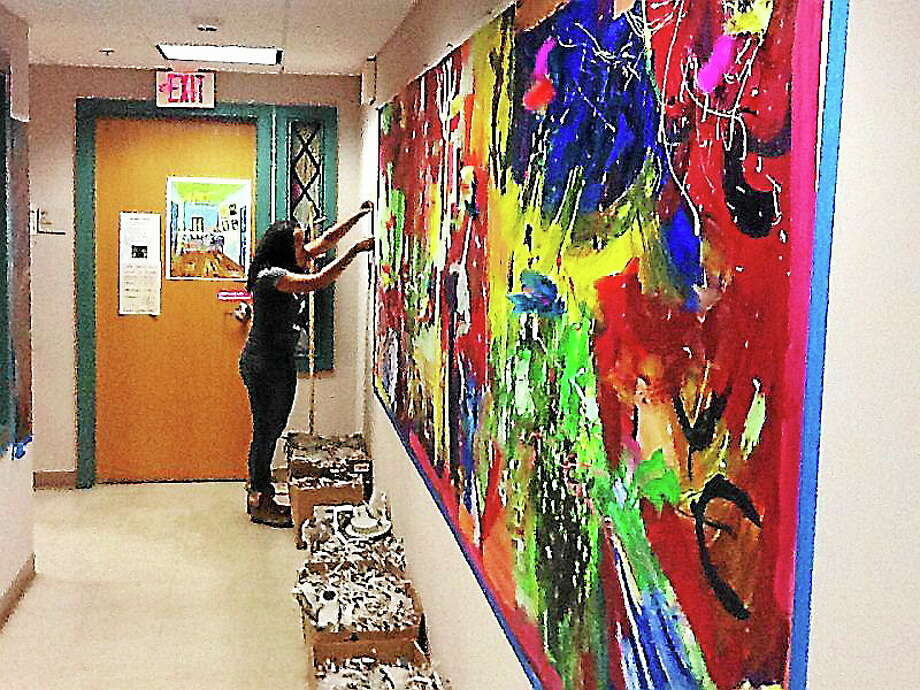 Volunteers from Dwight Hall at Yale, a service organization at the school, recently painted a large hallway area at Chapel Haven as part of a freshman day of service that tackled projects across the city. Students carefully put painters' tape around artwork done by students at Chapel Haven, a school that specializes in serving those with autism and other developmental disabilities. Photo: Journal Register Co.