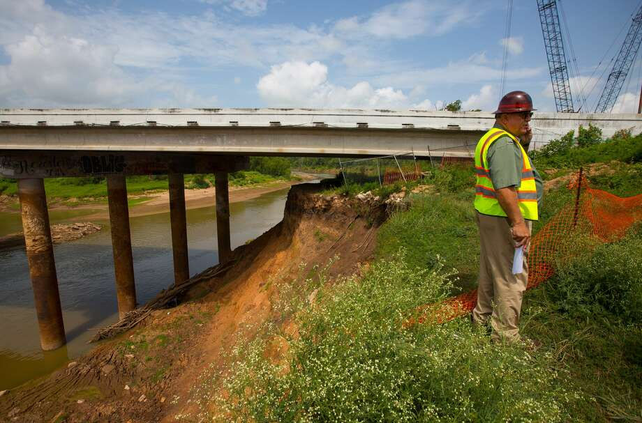 Mike Stone, with the Fort Bend County Toll Road Authority, walks the site where emergency work is being performed along the bank of the Brazos River around and underneath the Grand Parkway where the bank is suffering extreme erosion by floods in recent years, Tuesday, July 25, 2017. (Mark Mulligan / Houston Chronicle) Photo: Mark Mulligan/Mark Mulligan / Houston Chronicle