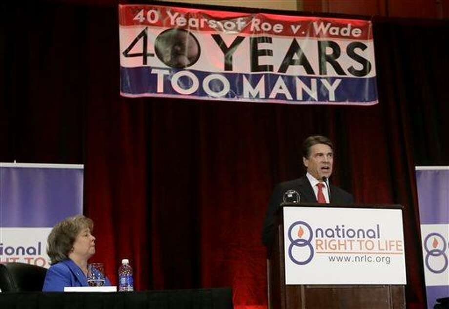 Carol Tobias, president of National Right To Life, left, watches as Gov. Rick Perry delivers a speech to a large audience in attendance at the national convention, Thursday, June 27, 2013, in Grapevine, Texas. The Republican has called a second special legislative session beginning July 1, allowing the GOP-controlled statehouse another crack at passing restrictions opponents say could shutter nearly all the abortion clinics across the country's second-largest state. (AP Photo/Tony Gutierrez) Photo: AP / AP