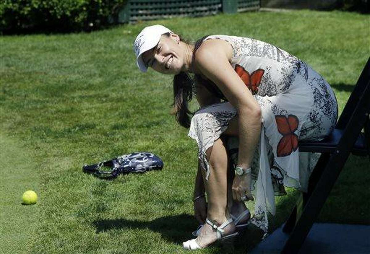 Newly inducted Tennis Hall of Famer Martina Hingis, of Switzerland, puts her shoes back on after having fun playing barefoot tennis on a show court adjacent to the Hall of Fame Tennis Museum in Newport, R.I. Sunday, July 14, 2013. (AP Photo/Elise Amendola)