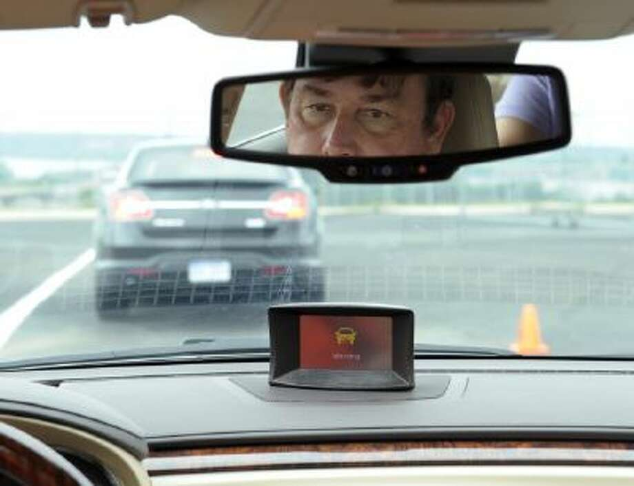Professional test driver Dave McMillan demonstrates the dashboard warning signal in a Buick Lacrosse at an automobile test area in Oxon Hill May 22, 2012.