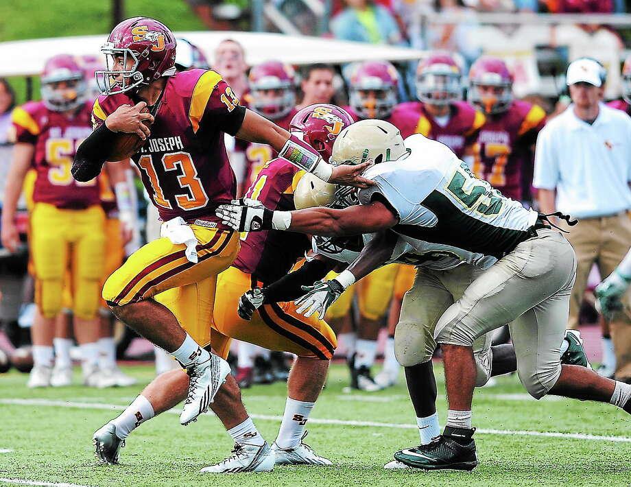 St. Joseph quarterback Jordan Vazzano slips out of the pocket past Notre Dame-West Haven's Matthew Abati in the third quarter. Photo: Peter Casolino — Register