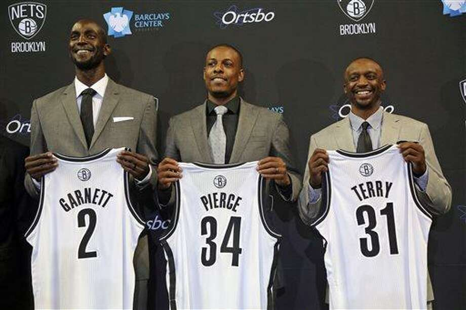 The Brooklyn Nets, from left, Kevin Garnett, Paul Pierce and Jason Terry, pose for photographers with their new jerseys during an NBA basketball news conference, Thursday, July 18, 2013 at Barlcays Center in New York. The  Nets introduced the trio they acquired in a blockbuster trade with the Boston Celtics. (AP Photo/Mary Altaffer) Photo: AP / AP