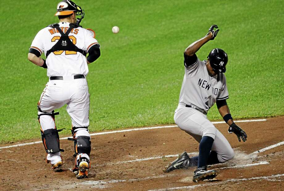 The Yankees' Alfonso Soriano slides safely into home past Orioles catcher Matt Wieters Thursday in Baltimore. Soriano was scratched Saturday in Boston. Photo: Patrick Semansky — The Associated Press   / AP