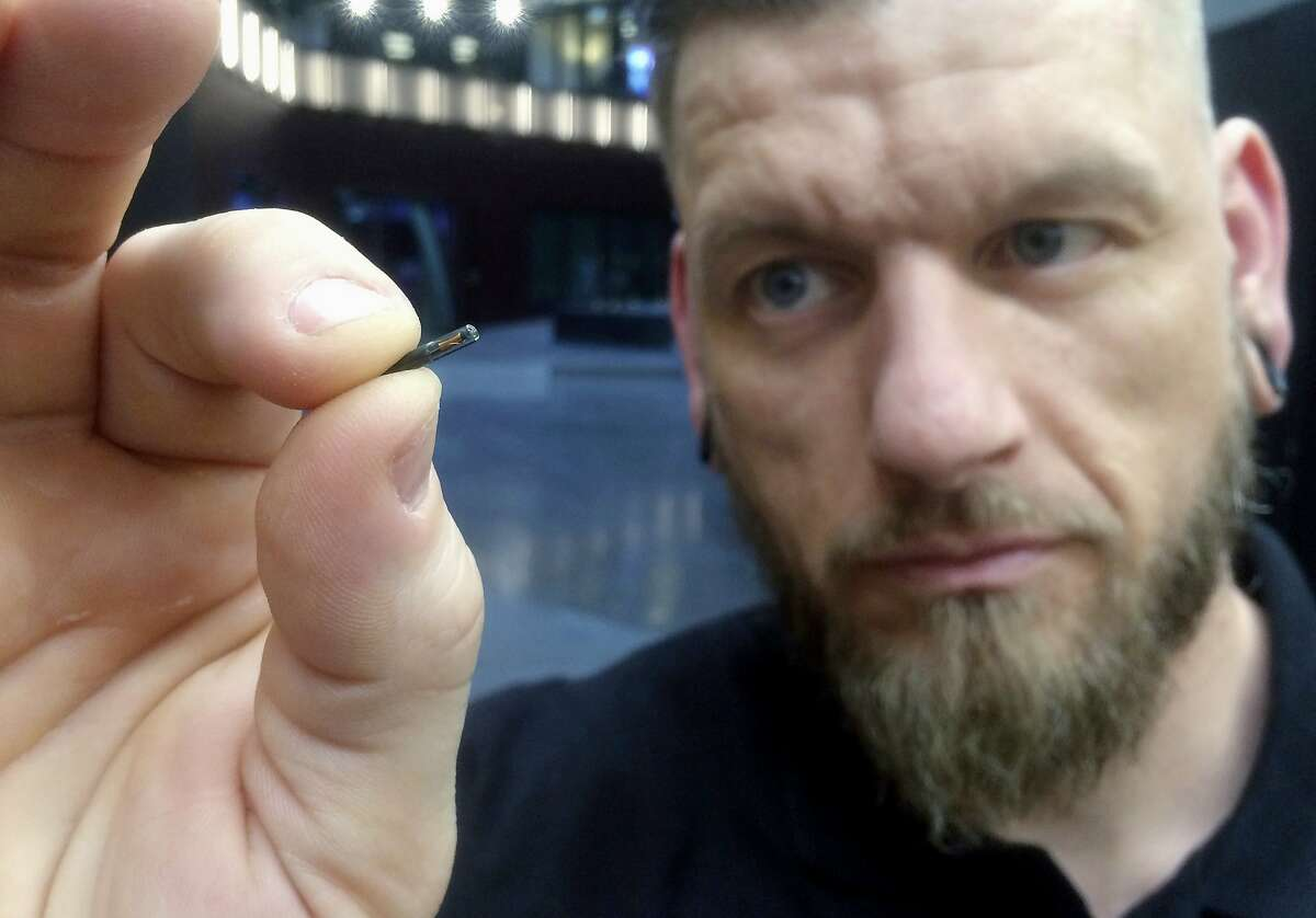 Jowan Osterlund from Biohax Sweden holds a small microchip implant, similar to those implanted into workers at Epicenter, a digital innovation business center in Stockholm.