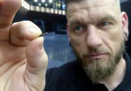 """FILE - In this March 14, 2017, file photo, Jowan Osterlund from Biohax Sweden, holds a small microchip implant, similar to those implanted into workers at the Epicenter digital innovation business center during a party at the co-working space in central Stockholm. Three Square Market in River Falls, Wis., is partnering with Sweden's BioHax International, offering to microchip its employees, enabling them to open doors, log onto their computers and purchase break room snacks with a simple swipe of the hand. More than 50 employees are voluntarily getting implants Aug. 1 at what the company is calling a """"chip party"""" at its River Falls headquarters. (AP Photo/James Brooks, File)"""