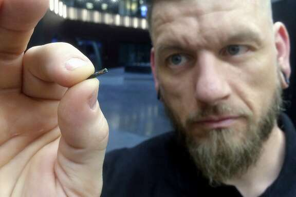 "FILE - In this March 14, 2017, file photo, Jowan Osterlund from Biohax Sweden, holds a small microchip implant, similar to those implanted into workers at the Epicenter digital innovation business center during a party at the co-working space in central Stockholm. Three Square Market in River Falls, Wis., is partnering with Sweden's BioHax International, offering to microchip its employees, enabling them to open doors, log onto their computers and purchase break room snacks with a simple swipe of the hand. More than 50 employees are voluntarily getting implants Aug. 1 at what the company is calling a ""chip party"" at its River Falls headquarters. (AP Photo/James Brooks, File)"