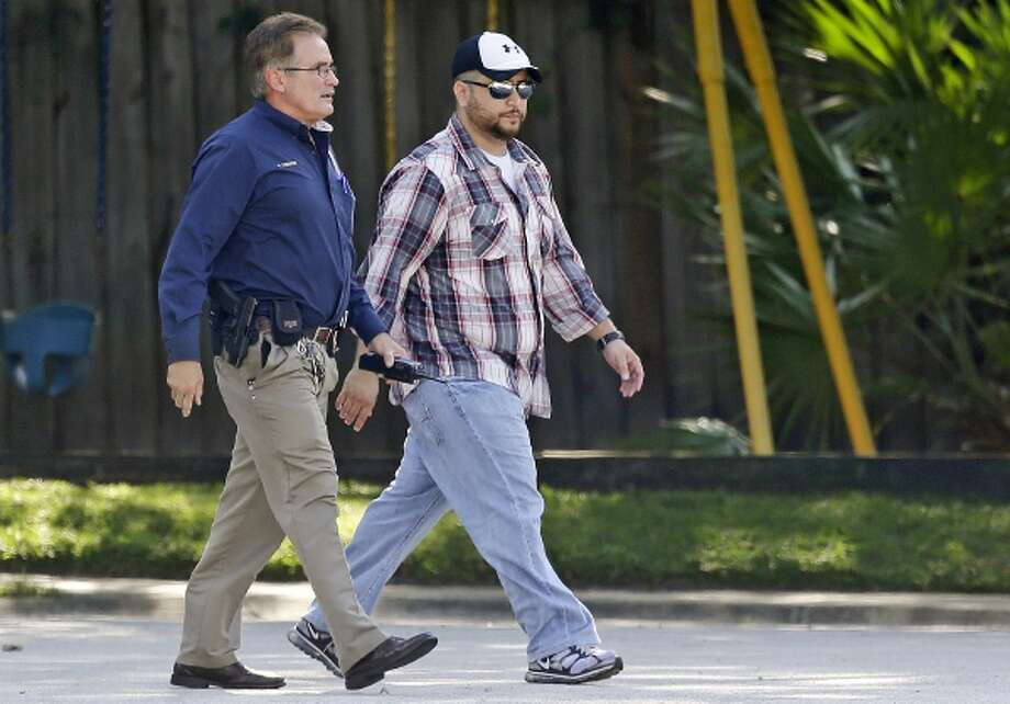 """In this Monday, Sept. 9, 2013 file photo, George Zimmerman, right, is escorted to a home by a Lake Mary police officer, in Lake Mary, Fla., after a domestic incident in the neighborhood where Zimmerman and his wife Shellie had lived during his murder trial. Whether they think he got away with murdering 17-year-old Trayvon Martin or that he was just a brave neighborhood watch volunteer """"standing his ground,"""" many Americans can't seem to get enough of George Zimmerman. And he can't seem to stop giving it to them. (AP Photo/John Raoux, File) Photo: AP / AP"""