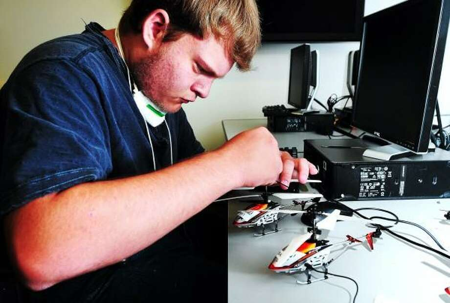 Brian Phillips, 17, of Milford attaches blades made using a 3D printer to a remote control helicopter at an engineering camp at the University of New Haven in West Haven on 7/18/2013. Arnold Gold/New Haven Register