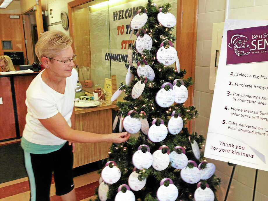 JOE AMARANTE -- NEW HAVEN REGISTER  Vicky Struk chooses an ornament from the Be a Santa to a Senior tree Monday morning at Stanley T. Williams School in North Branford. Photo: Journal Register Co.