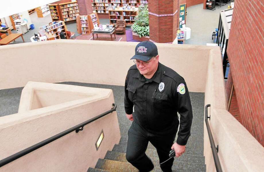 (Peter Casolino — New Haven Register)  Hamden Firefighter Kevin Delaney makes the rounds through the Miller Library on Monday afternoon. Delaney was stationed at the library because the fire alarm system was off-line. pcasolino@NewHavenRegister Photo: Journal Register Co.