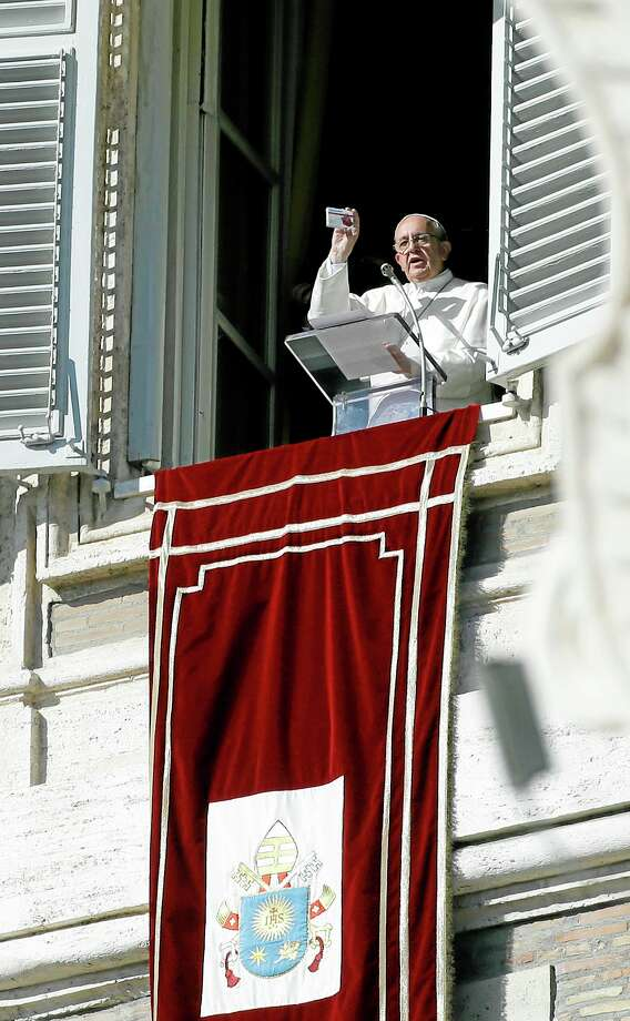 Pope Francis shows a rosary in a box designed to resemble a packets of pills, during his traditional Sunday's appearance from his studio overlooking St. Peter's Square at the Vatican, Sunday, Nov. 17, 2013. Joking that he's like a pharmacist, Pope Francis is promoting prayer as medicine for the heart. Appearing on Sunday at his studio window, Francis held up a rosary in a box designed to resemble a packets of pills. Francis' down-to-earth way of speaking in a style ordinary people can readily understand apparently has helped draw huger than usual crowds to St. Peter's Square for the traditional weekly papal appearances. About 80,000 tourists and Romans packed the square on a warm Sunday day. (AP Photo/Gregorio Borgia) Photo: AP / AP