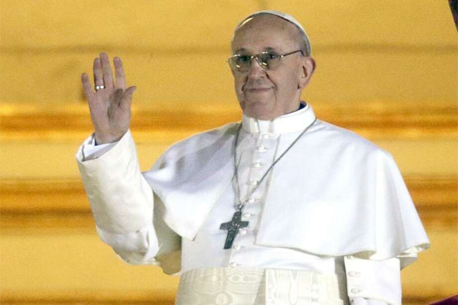 Pope Francis waves to the crowd from the central balcony of St. Peter's Basilica at the Vatican, Wednesday, March 13, 2013. Cardinal Jorge Bergoglio who chose the name of  Francis is the 266th pontiff of the Roman Catholic Church. (AP Photo/Gregorio Borgia) Photo: ASSOCIATED PRESS / AP2013