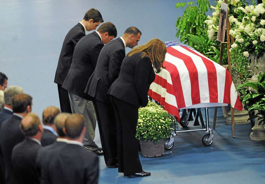 Florists and funeral directors bow their heads in front of the casket of TJ Lobraico during funeral services at the O'Neill Center in Danbury, Conn. on Friday, Sept. 13, 2013.  Staff Sgt. Lobraico, a member of the Air National Guard 105th Security Forces Squadron, was killed last Thursday after his unit was attacked near Bagram Airfield.  Hundreds of friends, family members, police officers and military members gathered to remember Lobraico.  He was buried in Sherman with full military honors following the ceremony. (AP Photo/ The News-Times, Tyler Sizemore) Photo: AP / The News-Times