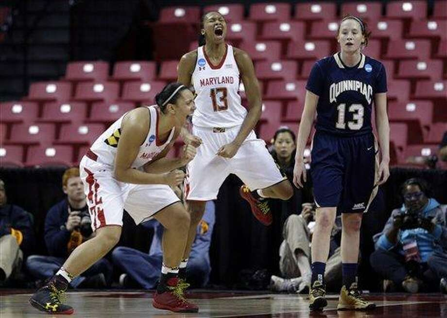 Maryland's Malina Howard, left, and Alicia DeVaughn, center, celebratea alongside Quinnipiac forward Camryn Warner after DeVaughn was fouled as she scored a basket during the first half of a first-round game in the women's NCAA college basketball tournament in College Park, Md., Saturday, March 23, 2013. (AP Photo/Patrick Semansky) Photo: AP / AP