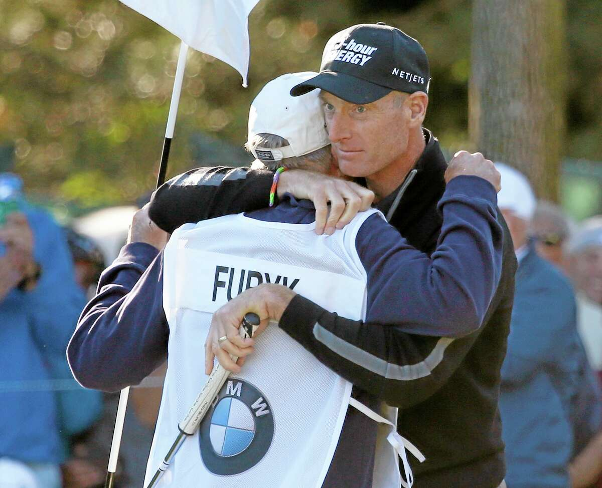 Jim Furyk hugs his caddie, Mike Cowan, after posting a 12-under-par 59, tying the PGA single-round record for lowest score, during the second round of the BMW Championship Friday at Conway Farms Golf Club in Lake Forest, Ill.