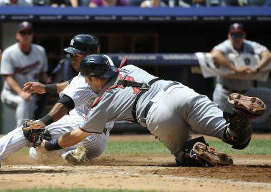 New York Yankees' Zoilo Almonte is tagged out at home plate by Minnesota Twins catcher Joe Mauer trying to score on Vernon Wells' fly ball in the third inning of a baseball game at Yankee Stadium on Sunday, July 14, 2013 in New York. Photo: ASSOCIATED PRESS / AP2013