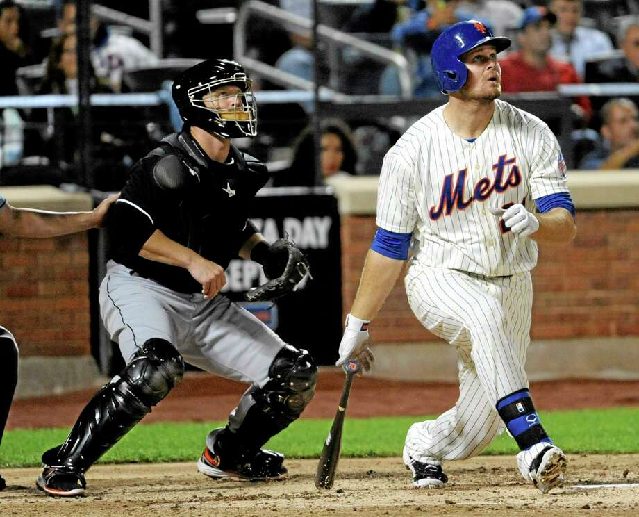 The Mets' Lucas Duda follows through on a three-run home run as Miami Marlins catcher Koyie Hill looks on during the sixth inning of Friday's game in New York. Photo: Bill Kostroun — The Associated Press   / FR51951 AP