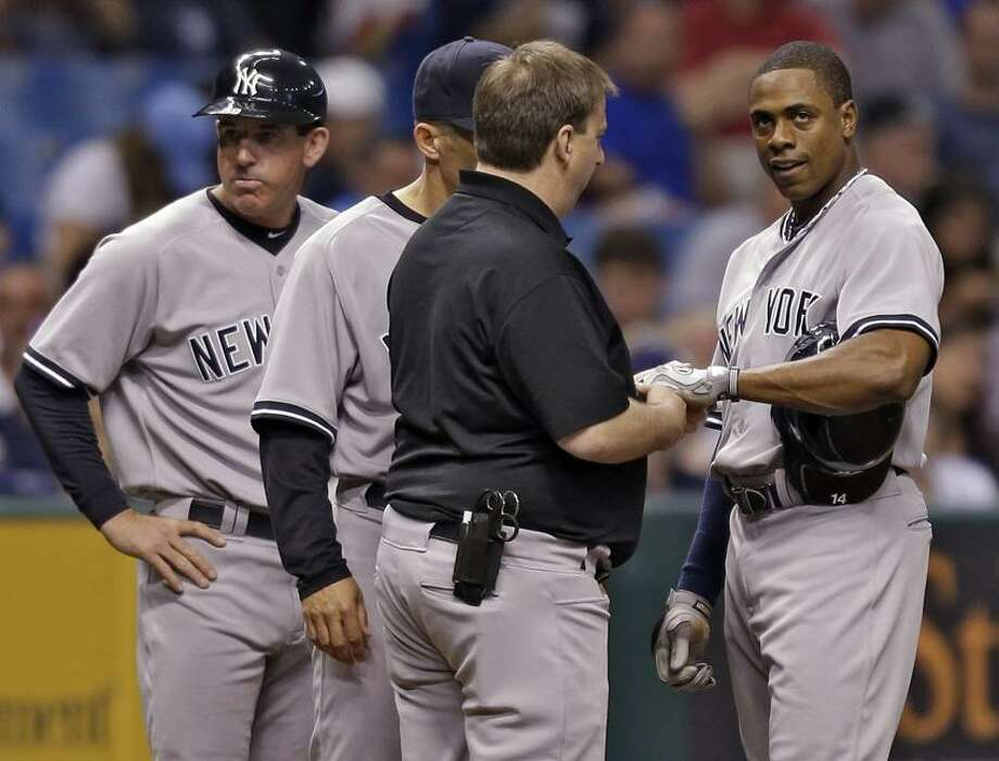 New York Yankees third base coach Rob Thomson, left, Joe Girardi (partially obscured) and a trainer look at Curtis Granderson's wrist during the fifth inning of a baseball game against the Tampa Bay Rays, Friday, May 24, 2013, in St. Petersburg, Fla. (AP Photo/Chris O'Meara) Photo: AP / AP