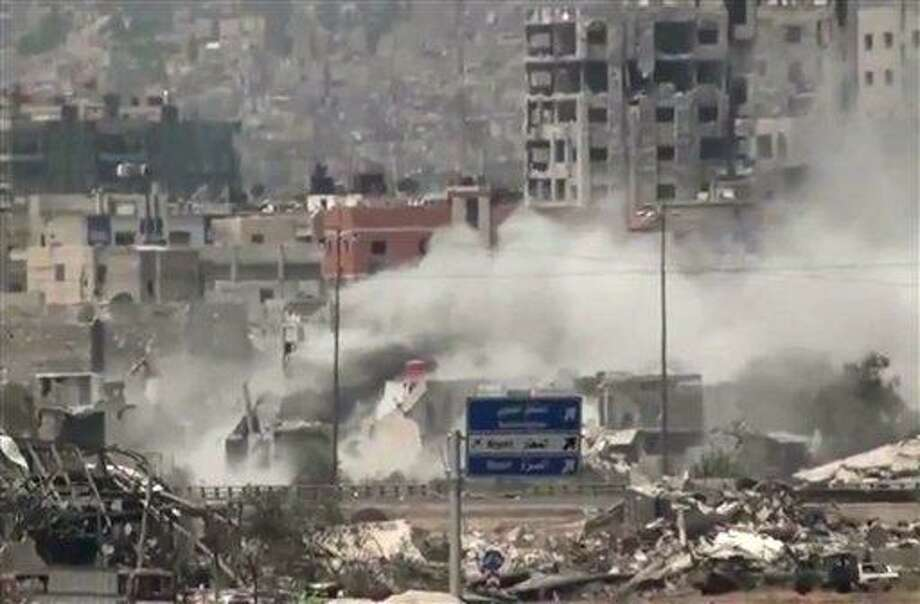 In this image taken from video obtained from Ugarit News, which has been authenticated based on its contents and other AP reporting, shows shelling of the Al-Qaboun neighborhood in rural Damascus, Syria, Monday, July 15, 2013. After seizing the momentum in recent months in Syria's civil war, President Bashar Assad's forces are on the offensive against the rebels on several fronts, including in Idlib province along the border with Turkey. Government forces are in firm control of the provincial capital of same name, while dozens of rebel brigades control the countryside.(AP Photo/Ugarit News via AP video) Photo: ASSOCIATED PRESS / AP2013