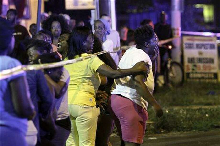 Family members react as they watch investigators at the scene of a fatal accident on Roosevelt Boulevard in the Olney section of Philadelphia on Tuesday evening July 16, 2013.  Philadelphia police are investigating whether cars may have been drag racing when a mother and two young sons were struck and killed attempting to cross a busy highway. The woman's two other sons ages 4 and 5 are in critical condition. (AP Photo/ Joseph Kaczmarek) Photo: AP / FR109827 AP