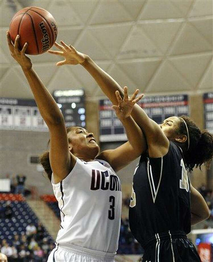 Connecticut's Morgan Tuck, left, goes up for a basket while guarded by Idaho's Ali Forde, right, during the first half of a first-round game in the women's NCAA college basketball tournament in Storrs, Conn., Saturday, March 23, 2013. Connecticut won 105-37. (AP Photo/Jessica Hill) Photo: ASSOCIATED PRESS / A2013