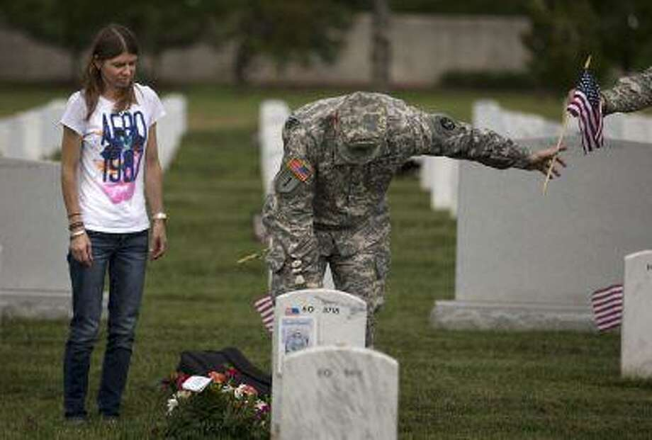 """Jennifer Henderson, of Winston-Salem, N.C., watches as Col. Jim Market, of the 3rd U.S. Infantry Regiment, also known as The Old Guard, places a flag at the grave site of her husband Sgt. 1st Class Christopher Henderson, who was killed in Afghanistan on June 17, 2007, at Arlington National Cemetery as part of the annual """"Flags-In"""" ceremony in preparation for Memorial Day on Thursday, May 23, 2013, in Arlington, Va. (AP Photo/Evan Vucci) Photo: AP / AP"""