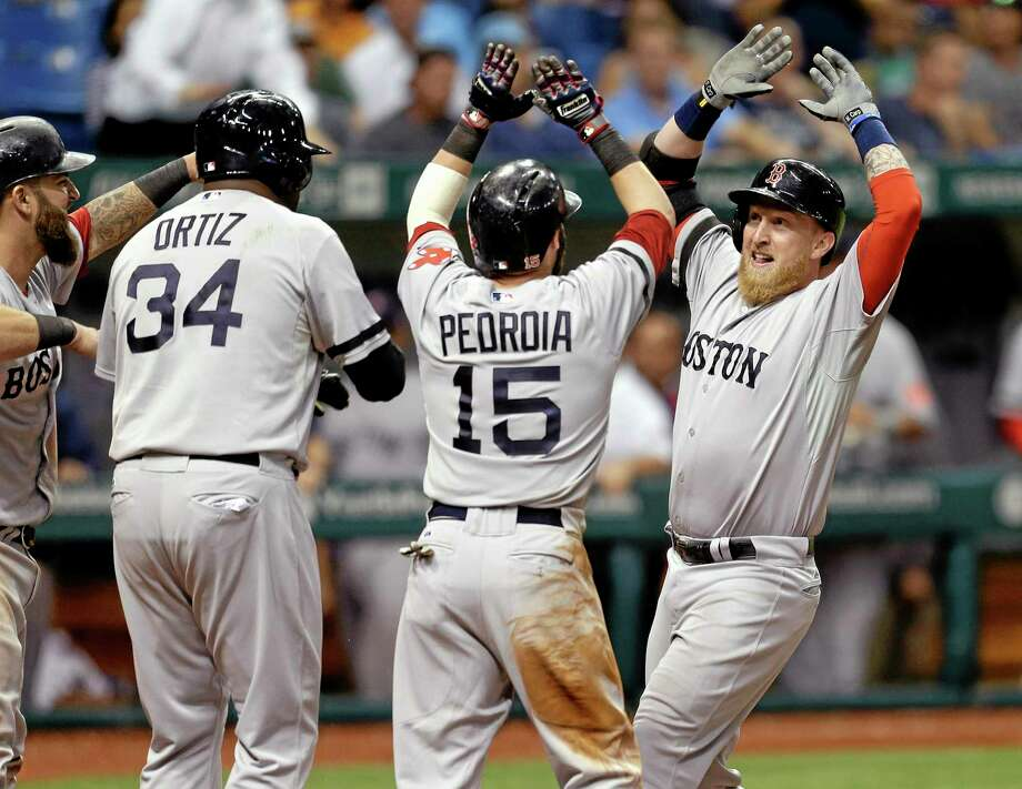 The Red Sox's Mike Carp, right, celebrates with teammates, from left, Mike Napoli, David Ortiz, and Dustin Pedroia after his 10th-inning grand slam off Tampa Bay Rays relief pitcher Roberto Hernandez. Photo: Chris O'Meara — The Associated Press   / AP