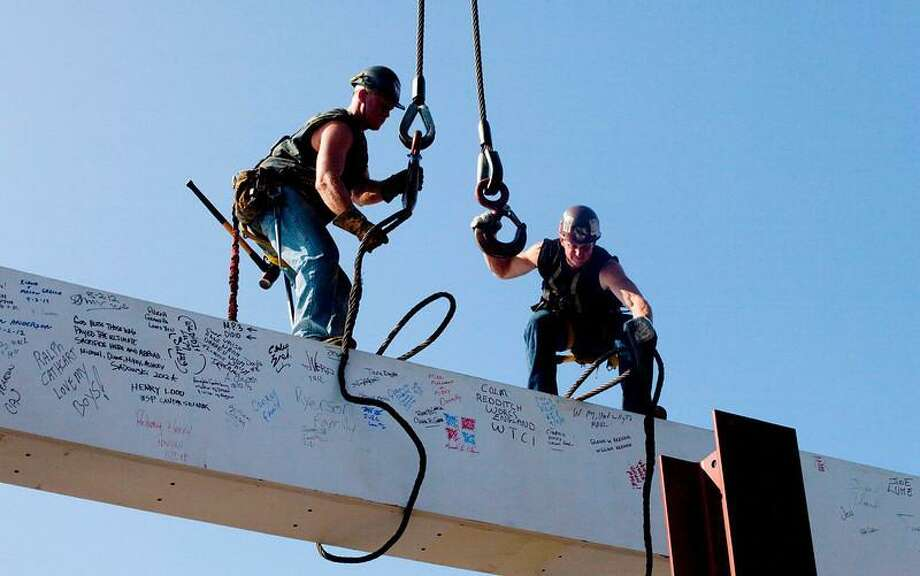 """In this file photo of Aug. 2, 2012, ironworkers James Brady, left, and Billy Geoghan release the cables from a steel beam after connecting it on the 104th floor of One World Trade Center in New York. The beam was signed by President Barack Obama with the notes: """"We remember,"""" """"We rebuild"""" and """"We come back stronger!"""" during a ceremony at the construction site June 14. Also adorned with the autographs of workers and police officers at the site, the beam will be sealed into the structure of the tower, which is scheduled for completion in 2014. (AP Photo/Mark Lennihan, File)"""