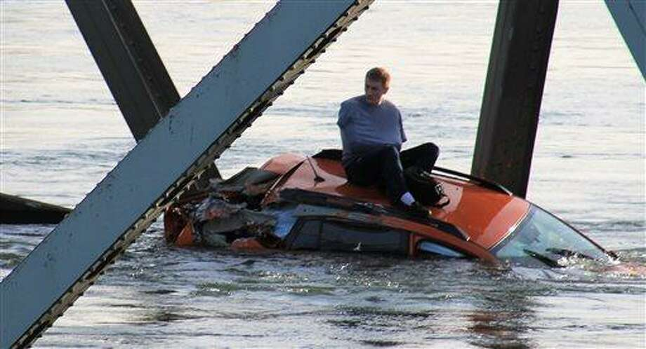 In this photo provided by Francisco Rodriguez, a man is seen sitting atop a car that fell into the Skagit River after the collapse of the Interstate 5 bridge there minutes earlier Thursday, May 23, 2013, in Mount Vernon, Wash. (AP Photo/Francisco Rodriguez) Photo: ASSOCIATED PRESS / AP2013