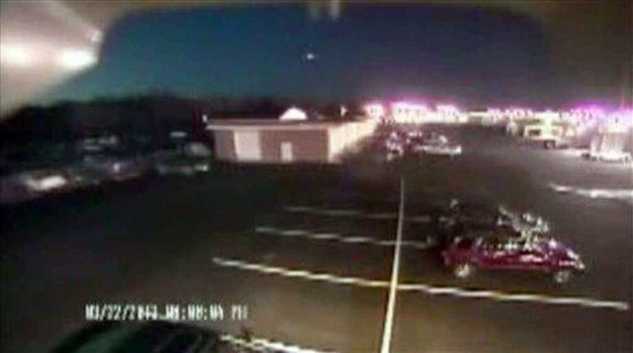 """In this image taken from video provided by Tom Hopkins of Hopkins Automotive Group, a bright flash of light, top center, streaks across the early-evening sky in what experts say was almost certainly a meteor coming down, Friday, March 22, 2013 in Seaford, Del. Bill Cooke of NASA's Meteoroid Environmental Office said the flash appears to be """"a single meteor event."""" He said it """"looks to be a fireball that moved roughly toward the southeast, going on visual reports."""" (AP Photo/Hopkins Automotive Group) Photo: AP / Tom Hopkins/Hopkins Automotive Group"""