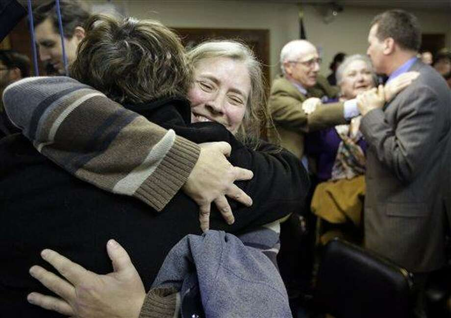 C. Kelly Smith, of Providence, R.I., center, a member of Marriage Equality Rhode Island, hugs fellow member Wendy Becker, left, also of Providence, after a house committee vote on gay marriage at the Statehouse, in Providence, Tuesday, Jan. 22, 2013. The House Judiciary Committee voted unanimously Tuesday to forward legislation to the House that would allow R.I. gay and lesbian couples to marry. (AP Photo/Steven Senne) Photo: AP / AP