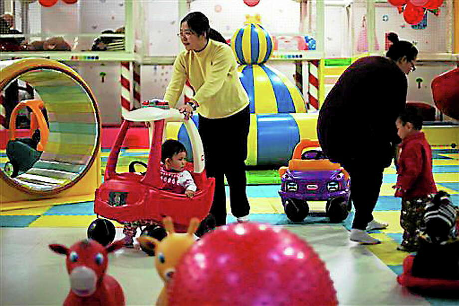 FILE - In this Jan. 10, 2013 photo, parents play with their children at a kid's play area in a shopping mall in Beijing.  China will loosen its decades-old one-child policy and abolish a much-criticized labor camp system, its ruling Communist Party said Friday, Nov. 15, 2013. The official Xinhua News Agency said the party announced the changes in a policy document following a key, four-day meeting of party leaders that ended Tuesday in Beijing. (AP Photo/Alexander F. Yuan, File) Photo: AP / AP