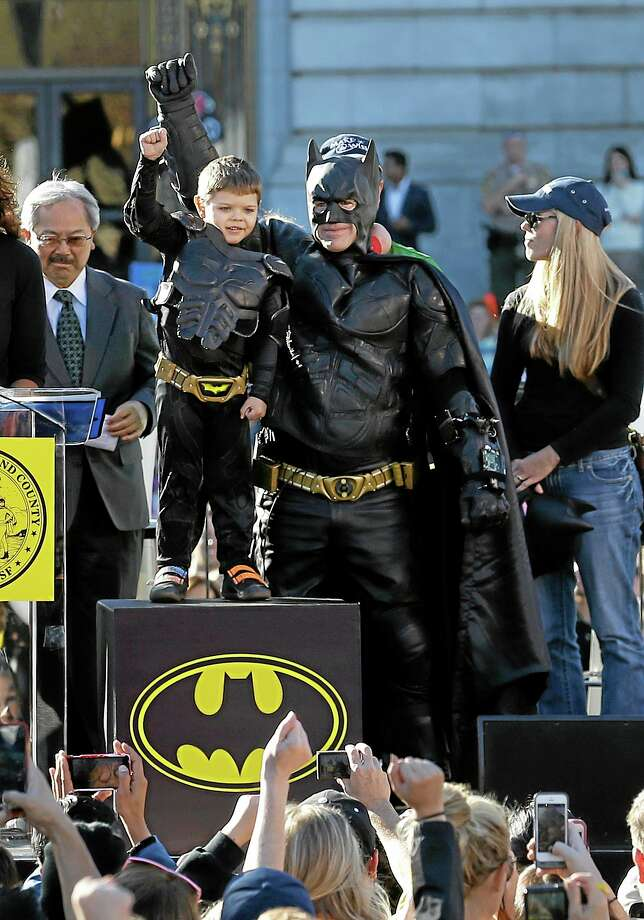 Miles Scott, dressed as Batkid, second from left, raises his arm next to Batman at a rally outside of City Hall with Mayor Ed Lee, left, and his mother, Natalie Scott, in San Francisco Friday. Photo: Jeff Chiu — The Associated Press       / AP