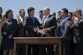 Senate President pro Tempore Kevin de Le�n and Gov. Jerry Brown shake hands following a signing ceremony at Treasure Island on Tuesday, July 25, 2017, in San Francisco, Calif. Gov. Jerry Brown signed AB 398, a bill extending California's cap-and-trade system. He signed it on the same spot where former California Gov. Arnold Schwarzenegger signed the state's landmark 2006 climate change law, AB 32, which led to the creation of the cap-and-trade system.