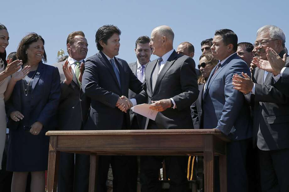 Senate President pro Tempore Kevin de Le�n and Gov. Jerry Brown shake hands following a signing ceremony at Treasure Island on Tuesday, July 25, 2017, in San Francisco, Calif. Gov. Jerry Brown signed AB 398, a bill extending California's cap-and-trade system. He signed it on the same spot where former California Gov. Arnold Schwarzenegger signed the state's landmark 2006 climate change law, AB 32, which led to the creation of the cap-and-trade system. Photo: Santiago Mejia, The Chronicle