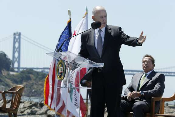 Gov. Jerry Brown gives his remarks during a signing ceremony at Treasure Island on Tuesday, July 25, 2017, in San Francisco, Calif. Gov. Jerry Brown signed AB 398, a bill extending California's cap-and-trade system. He signed it on the same spot where former California Gov. Arnold Schwarzenegger (seen in the background) signed the state's landmark 2006 climate change law, AB 32, which led to the creation of the cap-and-trade system.