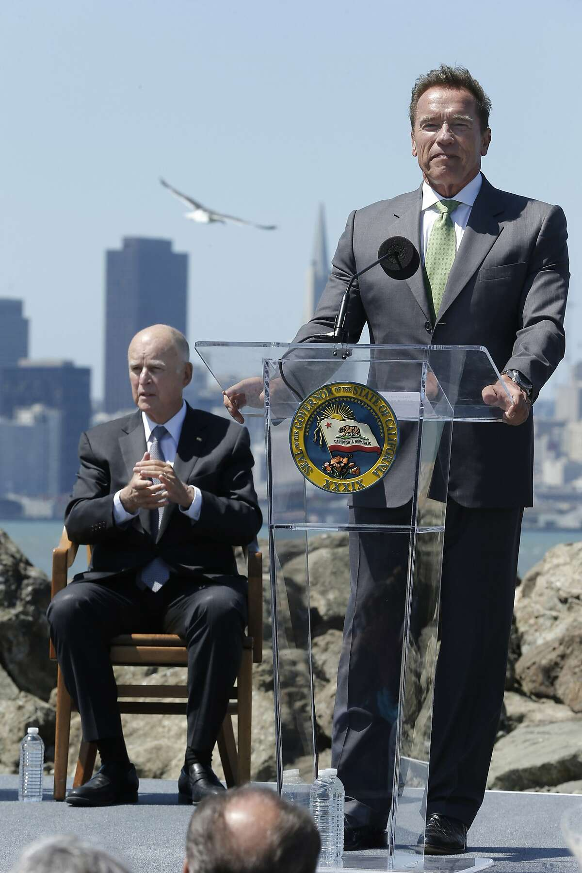 Former California Gov. Arnold Schwarzenegger gives his remarks during a signing ceremony at Treasure Island on Tuesday, July 25, 2017, in San Francisco, Calif. Gov. Jerry Brown (seen in the background) signed AB 398, a bill extending California's cap-and-trade system. He signed it on the same spot where former California Gov. Arnold Schwarzenegger signed the state's landmark 2006 climate change law, AB 32, which led to the creation of the cap-and-trade system.
