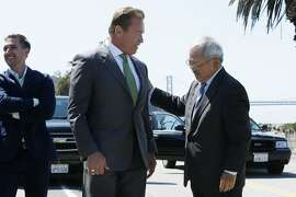 Former California Gov. Arnold Schwarzenegger (center) and Mayor Ed Lee greet each other before a signing ceremony at Treasure Island on Tuesday, July 25, 2017, in San Francisco, Calif. Gov. Jerry Brown signed AB 398, a bill extending California's cap-and-trade system. He signed it on the same spot where former California Gov. Arnold Schwarzenegger signed the state's landmark 2006 climate change law, AB 32, which led to the creation of the cap-and-trade system.